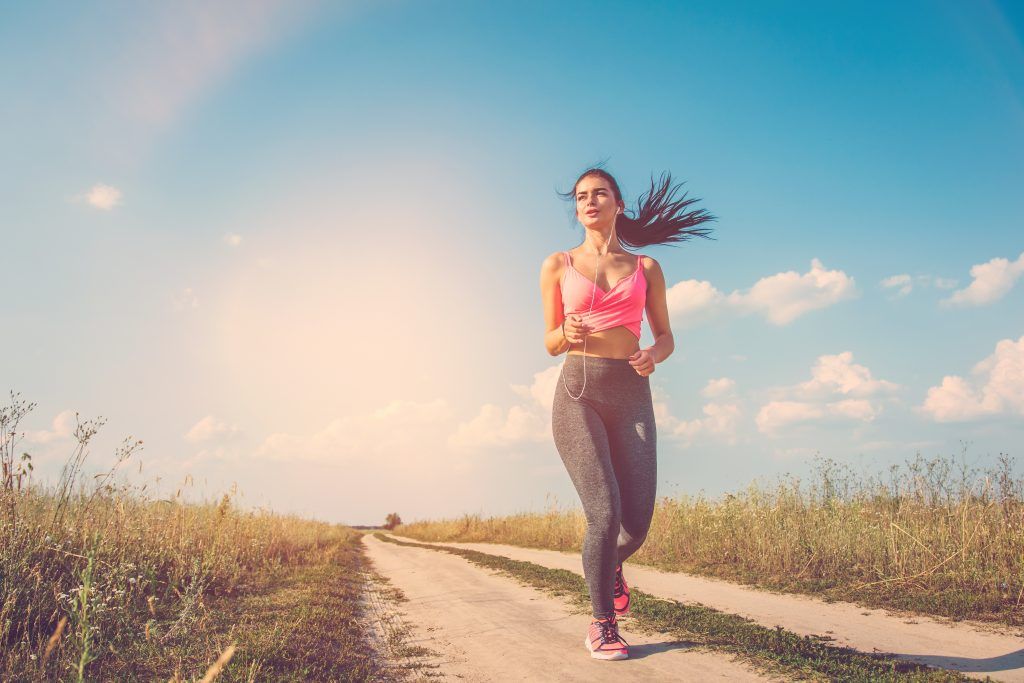 The woman running on the dirt road on the sunny background